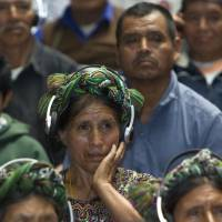 Survivors testify: An Ixil Indian woman, a relative of a civil war victim, uses earphones to listen to translations at the trial of Efrain Rios Montt in Guatemala City on Thursday. | AP