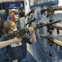 A young man who chose not to give his name sizes up an assault rifle during the annual convention a day earlier. | AP