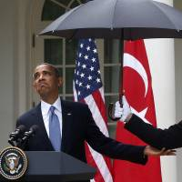 When it rains, it pours: President Barack Obama looks to see if it is still raining as a U.S. Marine holds an umbrella for him during his joint news conference with Turkish Prime Minister Recep Tayyip Erdogan on Thursday in the White House Rose Garden in Washington. | AP
