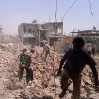 War zone: This citizen journalism image provided by Qusair Lens shows Syrians inspecting the rubble of damaged buildings following airstrikes by government forces on Qusair on Saturday. | AP