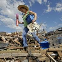No kicks on Route 66: A resident of Moore, Oklahoma, salvages items from a friend's tornado-ravaged home on  Wednesday. | AP