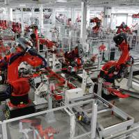 The future of jobs?: Robots assemble Tesla Model S sports cars at the state of the art Tesla factory in Fremont, California. | AP
