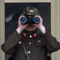 Through their eyes: A North Korean soldier looks through a pair of binoculars at the border village of Panmunjom, which has separated the two Koreas since the Korean War, in Paju, South Korea, on May 14. | AP