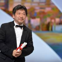 Looking up: Japanese director Hirokazu Koreeda takes the stage at the 66th Cannes Film Festival after being awarded the Prix du Jury for the film 'Like Father, Like Son' on Sunday. | AFP-JIJI