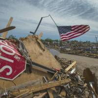Tornado alley: An American flag flies over a mound of debris in a neighborhood in Moore, Oklahoma, on Thursday. Soon after a killer tornado blew through the town, in the suburbs of Oklahoma City, a few days before, residents began displaying flags as symbols of hope and unity. | THE WASHINGTON POST