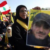 In mourning: A Hezbollah supporter in the village of Mashghara, Lebanon, on Saturday holds a poster of her son, who was killed during a battle in Syria 40 days earlier. | AP