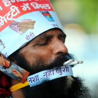 Puffing away: Rajendra Kumar Tiwari, a performer, smokes two cigarettes at  the same time as he campaigns with a magician during World No Tobacco Day in Allahabad on Friday. | AFP-JIJI