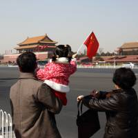 Focal point: A young girl waves a Chinese flag near Beijing's Tiananmen Square in March. | BLOOMBERG
