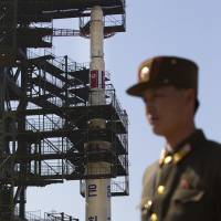 Tall order: A North Korean soldier guards an Unha-3 rocket in Tongchang-ri ahead of its launch in April 2012. The rocket exploded about a minute after takeoff. | AP