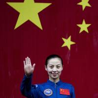 Long space march: Chinese female astronaut Wang Yaping waves upon her arrival at the Jiuquan satellite launch center near Jiuquan, in western Gansu province, on Monday. | AP