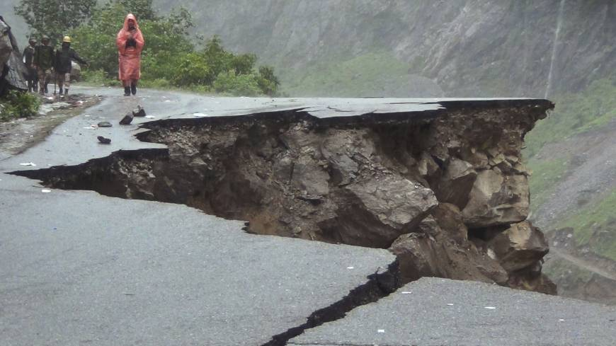 Dangerous path: Villagers examine a collapsed stretch of the Rishikesh-Mana highway on Monday after torrential rain wreaked havoc in the Indian state of Uttarakhand.