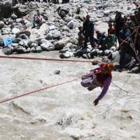 Survivor: A stranded pilgrim is carried on ropes rigged up by Indian soldiers over a river in Uttarakhand state Friday. | AFP-JIJI