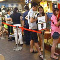 Dem bones: Consumers line up to get their paws on a Hello Kitty character toy in a skeleton outfit at a McDonald's restaurant in Singapore on  Thursday. | AFP-JIJI