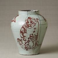 A felicitous pair: A Joseon Dynasty porcelain jar with a tiger and magpie design in underglaze copper red. | COURTESY OF THE JAPAN FOLK CRAFTS MUSEUM