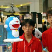 Flying: Taiyo Kogyo Co. employees demonstrate the company's radio-controlled helicopter toy of anime character Doraemon at a Tokyo toy show in 2005. In 2008, Doraemon was appointed by the Foreign Ministry as an ambassador for cultural diplomacy. | BLOOMBERG