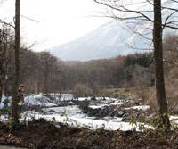 Nature's bounty: An angler snapped from my study window (left) casts his line into the Torii River, which is dwarfed in this corner of Nagano Prefecture by mighty Mount Kurohime as it rushes on its way to the Sea of Japan. | C.W. NICOL PHOTOS