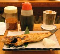 Keeping it traditional: A typical dish of grilled fish at Uosan Sakaba, served with a glass of sake .
