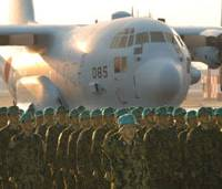 Lines of duty: ASDF members at Komaki, Aichi Prefecture, stand before an aircraft set to take them to Iraq in December 2003. | AP PHOTO