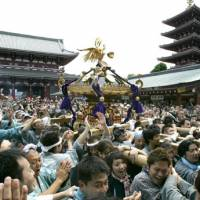 Death and renewal: People carry a mikoshi (portable shrine), associated with Shintoism, in the compound of Asakusa's Buddhist Sensoji Temple in Tokyo. | AP PHOTO