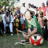Testing time: Eriko Mukoyama plays the nyatiti before 200 Luo people in the village of Karapul near Lake Victoria, Kenya, in November 2005. With this performance, she was certified by the Luo as the first female master of their traditional instrument. | ERIKO MUKOYAMA PHOTO