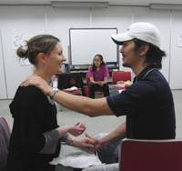 Breath easy: A pregnant woman and her partner practice pain-relieving techniques during a recent childbirth education class in Tokyo taught by Brett Iimura. | COURTESY OF KAZUHIKO IIMURA