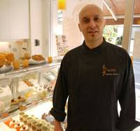 Epicurean delights: Antoine Santos stands beside a display case filled with desserts at his pastry shop and school Ecole Criollo in Toshima Ward, Tokyo. | TOMOKO OTAKE PHOTO