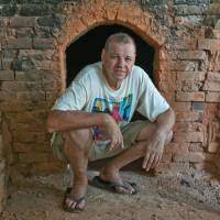 DIY: Paul Lorimer squats in front of a kiln he built near his home on the southeastern coast of Okinawa Island. | STEPHEN MANSFIELD