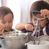 Baking friends: Two of the young cooks get to grips with stirring ingredients into the cake mix. | DANIELLE DEMETRIOU