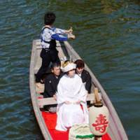 Life's journey: A make-believe bride and her groom glide in traditional style down the Mae River in Itako to the delight of visitors.