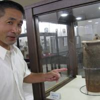 Idojiri Archaeological Museum director Seishi Higuchi (right) points to one of his star finds from the Jomon era. | WINIFRED BIRD