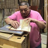 Motonobu Murayama, whose Yamayasu company supplies the materials for tea houses and also constructs them, open an archived 3-D paper scale model of one of their creations. | KIT NAGAMURA PHOTO