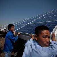 Where the sun don't shine: Workers install solar panels near Tianjin, China, in June of last year. | AFP-JIJI
