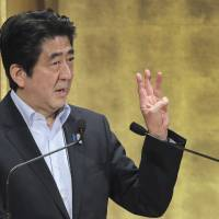 Everything comes in threes: Prime Minister Shinzo Abe discusses the third 'arrow' of his growth strategy during a speech in Tokyo on Wednesday. | AP