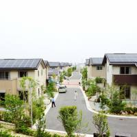 Sunny days: Visitors inspect solar-powered residential quarters developed by Daiwa House Industry Co. in Sakai, Osaka Prefecture, on Thursday. | KYODO