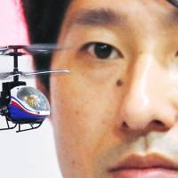 An employee of Japanese toy and home appliances maker CCP Co. flies a Nano-Falcon, the world's smallest infrared, remote-controlled helicopter, at the International Tokyo Toy Show on Thursday. | AP