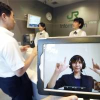 Sign of the times: A JR East operator uses sign language Monday on an iPad screen in Shinagawa Station as the railway began testing a new service for the hearing-impaired. | KYODO