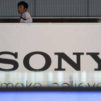 The big print: A man stands above a Sony Corp. sign at the company's headquarters in Tokyo on May 22. | BLOOMBERG