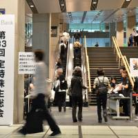 Shares and share alike: Softbank Corp. investors enter the venue for the annual shareholders' meeting Friday morning at the Tokyo International Forum conference hall. | AFP-JIJI