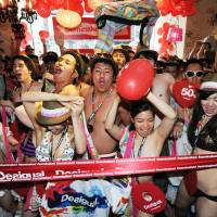 Dressed down: One hundred shoppers in swimwear start the 'semi-naked party' at the Desigual shop in Tokyo's Harajuku district Saturday. | AFP-JIJI