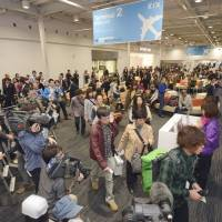 Waiting to go: Passengers bide their time with media crews in Kansai International Airport's departure lobby for budget carriers in October. | KYODO