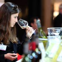 Sniffing out the fakes: A woman tastes wine during the Vinexpo trade fair in Bordeaux, on June 17. Among the issues covered at the world's biggest wine expo was the issue of wine forgery and how to prevent it. | AFP-JIJI