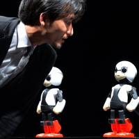 Space-bound roommate: University of Tokyo robot engineer Tomotaka Takahashi chats with Kirobo (right) and its backup robot, Mirata, in Tokyo on Wednesday. | AFP-JIJI