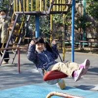 Can't a kid have fun anymore?: A girl plays on a swing at a playground in Tokyo in March. As Japan's population declines, intolerance of children and the noise they make is increasing as society gets less used to hearing them. | AFP-JIJI