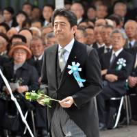 Nostalgist?: Prime Minister Shinzo Abe offers a chrysanthemum during an annual memorial service at Tokyo's Chidorigafuchi National Cemetery, the tomb for unknown war victims, on May 27. | AFP-JIJI