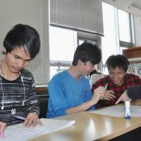 Studying up: Foreign youths study for the Japanese high school entrance exam during a class in Kani, Gifu Prefecture, in April. They were taking part in a program overseen by the nonprofit organization Kani International Exchange Association. | KYODO