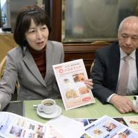 All ears: Maruberu Co. President Hiroshi Mitsuzawa listens as a single-mother employee explains about food services for corporate customers in Taito Ward, Tokyo, in late April. | KYODO