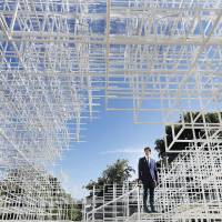 A man stands inside the Serpentine Gallery 2013 Pavilion, designed by Japanese architect Sou Fujimoto, in London's Kensington Gardens, on Tuesday. Occupying some 357 sq. meters of lawn in front of the gallery, Fujimoto's creation, using 20 mm steel tubes and glass, also features a cafe and space for visitors to interact. | AP