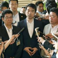 Meet the press: Osaka Mayor Toru Hashimoto fields questions from reporters Thursday at the prime minister's office while standing beside Osaka Gov. Ichiro Matsui. | KYODO