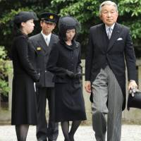 A family affair: Emperor Akihito visits the grave of Prince Tomohito of Mikasa in Tokyo's Bunkyo Ward Monday, followed by the late prince's daughters, Princesses Akiko (center) and Yoko. Empress Michiko did not accompany the Emperor, having suspended her official duties for the beginning of the week to recover from fatigue. | KYODO