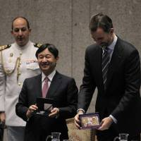 Collector's items: Crown Prince Naruhito (left) and Spanish Crown Prince Felipe (right) exchange commemorative coins during the opening of the Spanish-Japanese Business Cooperation Meeting at the House of Mint in Madrid on Tuesday. | AP